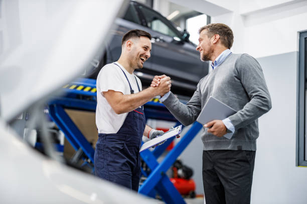 Happy auto mechanic and his manager greeting in a repair shop. stock photo