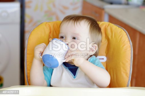istock happy baby boy drink from a cup 451425111