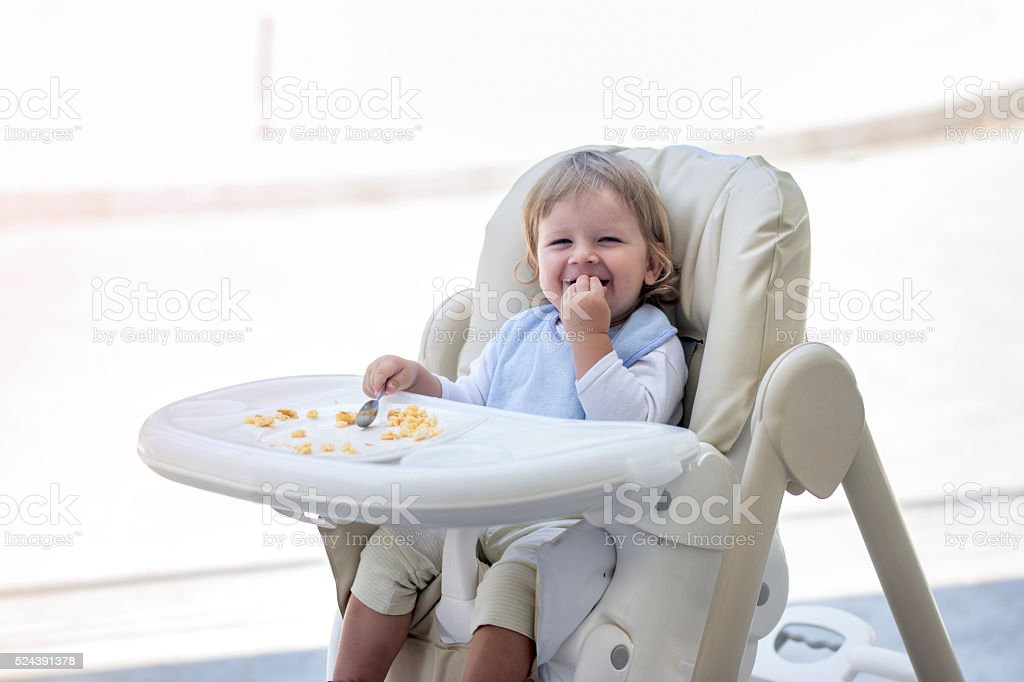 Happy baby boy eating breakfast in high chair. stock photo