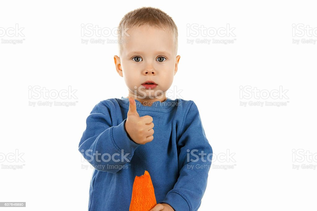 Happy baby boy eating carrot, isolated stock photo