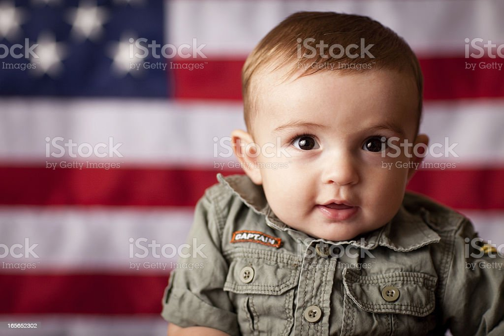 Happy Baby Boy in Camo by American Flag stock photo