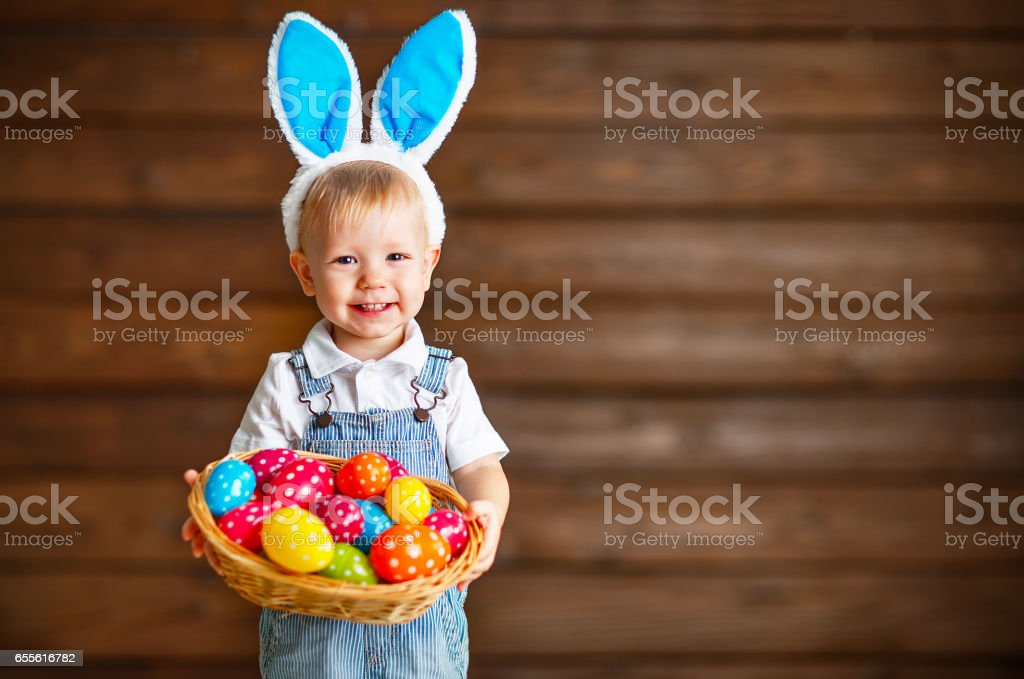 Happy baby boy in Easter bunny suit with basket of eggs stock photo