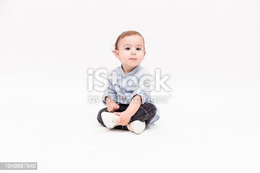 Happy baby boy is sitting on white background, studio shot