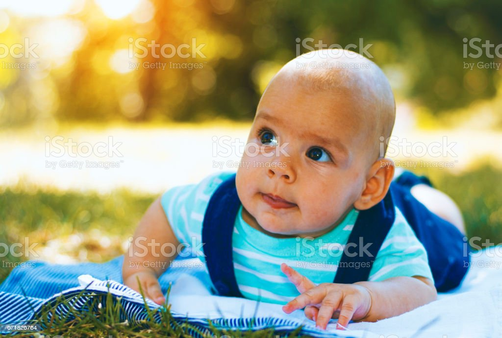 Happy baby boy laying outside on blanket. Looking Up stock photo