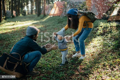 istock Happy baby boy making his first steps on grass in forest. 874111284