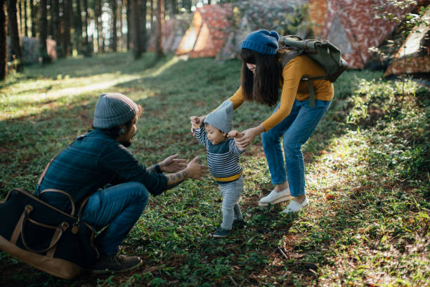 Happy baby boy making his first steps on grass in forest. stock photo