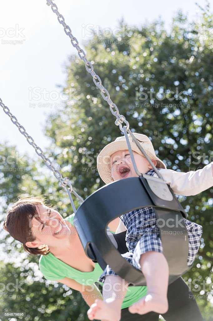 Happy Baby Boy Sitting in Playground Swing Outdoors With Mom stock photo