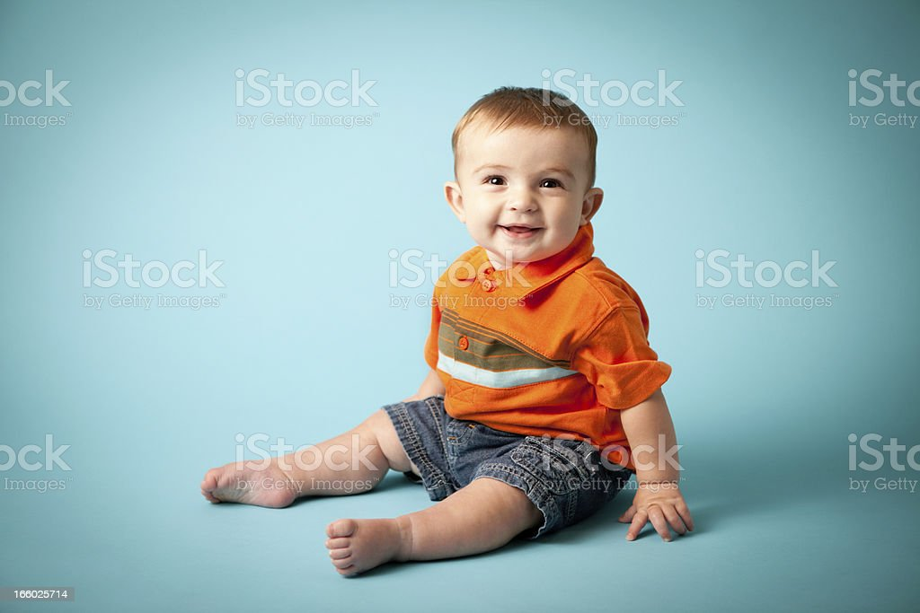 Happy Baby Boy Smiling on Teal Background stock photo