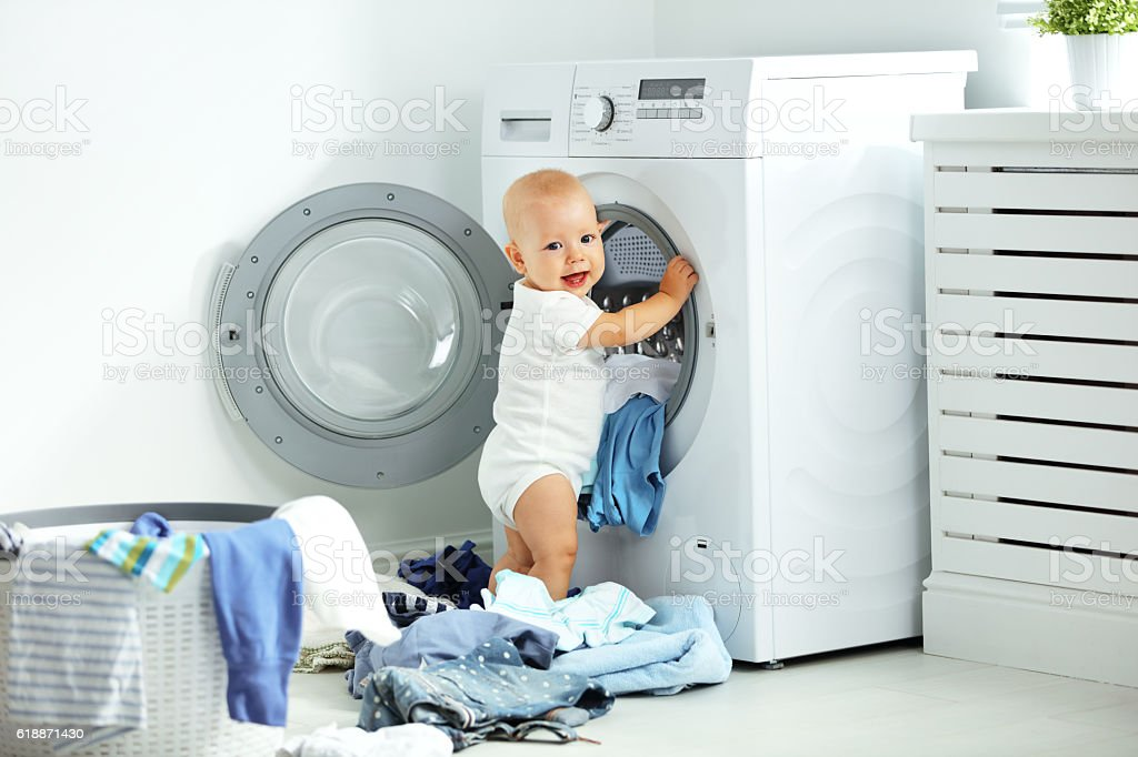 happy baby boy  to wash clothes and laughs in laundry stock photo