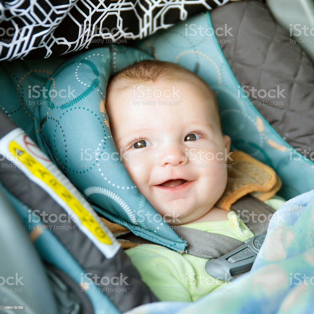 Happy baby buckled into rear-facing car seat stock photo