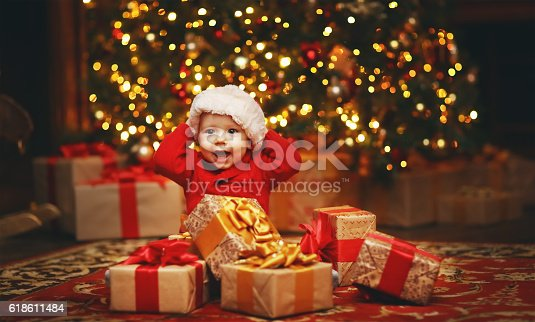 istock Happy baby by Christmas tree with gifts 618611484