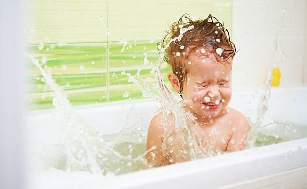 glücklich baby kind taucht in ein bad streusel und spielt - mädchen dusche stock-fotos und bilder