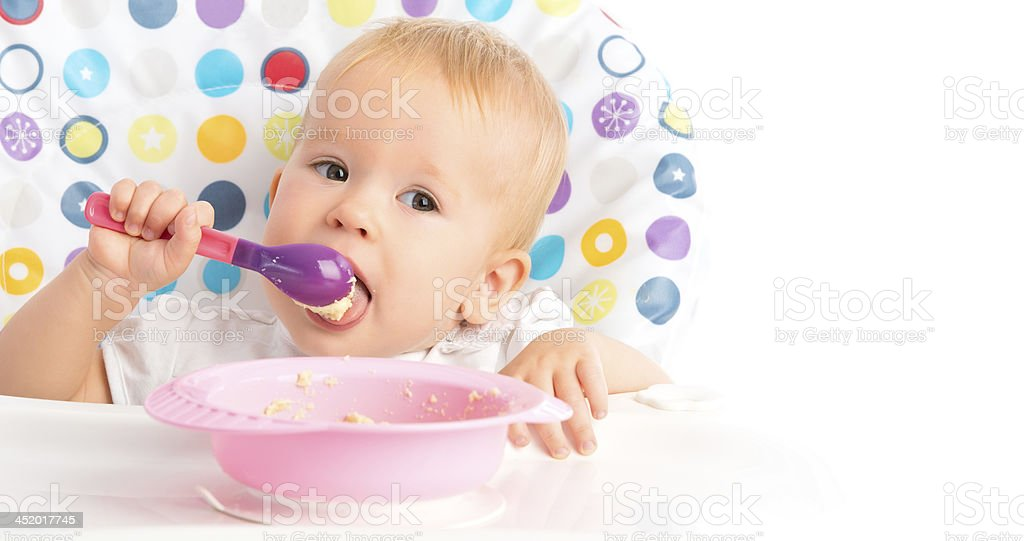 happy baby child eats itself with a spoon royalty-free stock photo