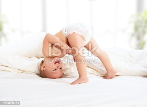 1084486306 istock photo happy baby child playing   in bed 460926431