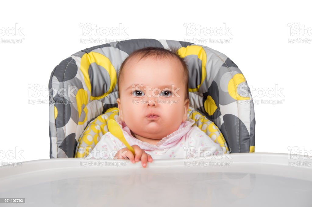 happy baby child sitting in chair with a spoon royalty-free stock photo