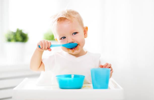 Happy baby eating himself - foto de acervo