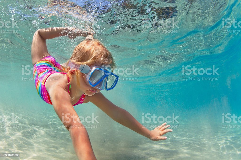 Happy baby girl dive underwater in sea pool stock photo