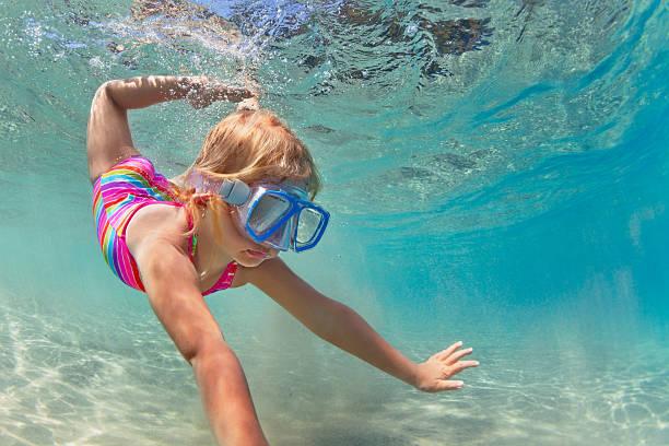 Happy baby girl dive underwater in sea pool stock photo