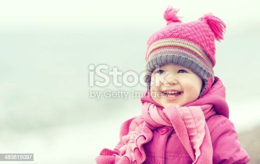 istock Happy baby girl in a pink hat and scarf 483815097