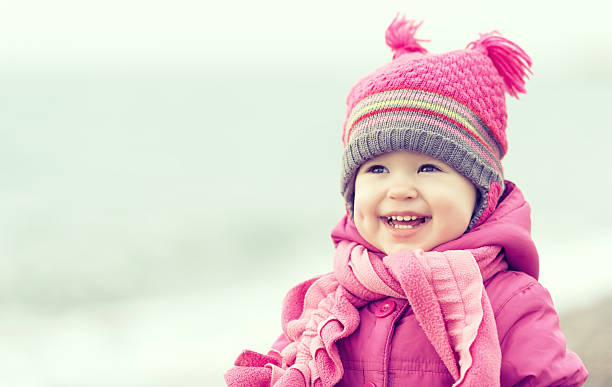 happy baby girl in a pink hat and scarf - warm clothing stock photos and pictures