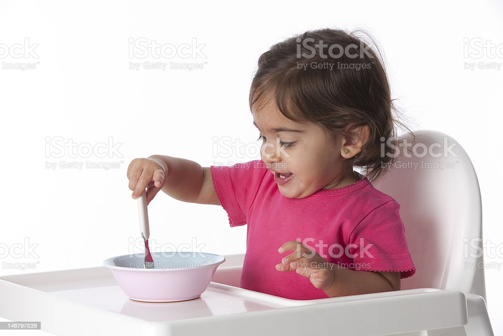 Happy Baby girl is eating by herself royalty-free stock photo