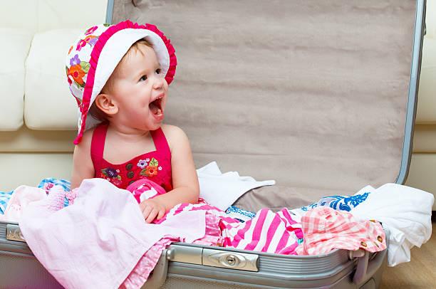 happy baby mädchen ist auf reise-koffer packen - kleinkind busy bags stock-fotos und bilder
