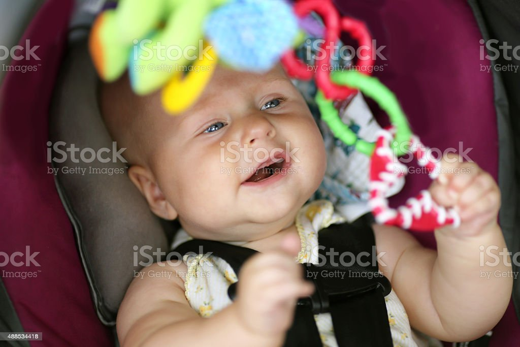 Happy Baby Girl Playing in Car Safety Seat stock photo