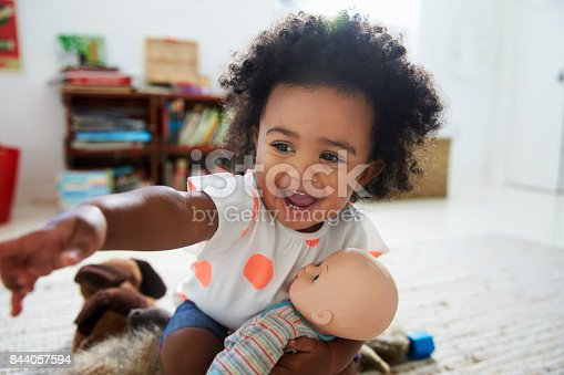 istock Happy Baby Girl Playing With Doll In Playroom 844057594