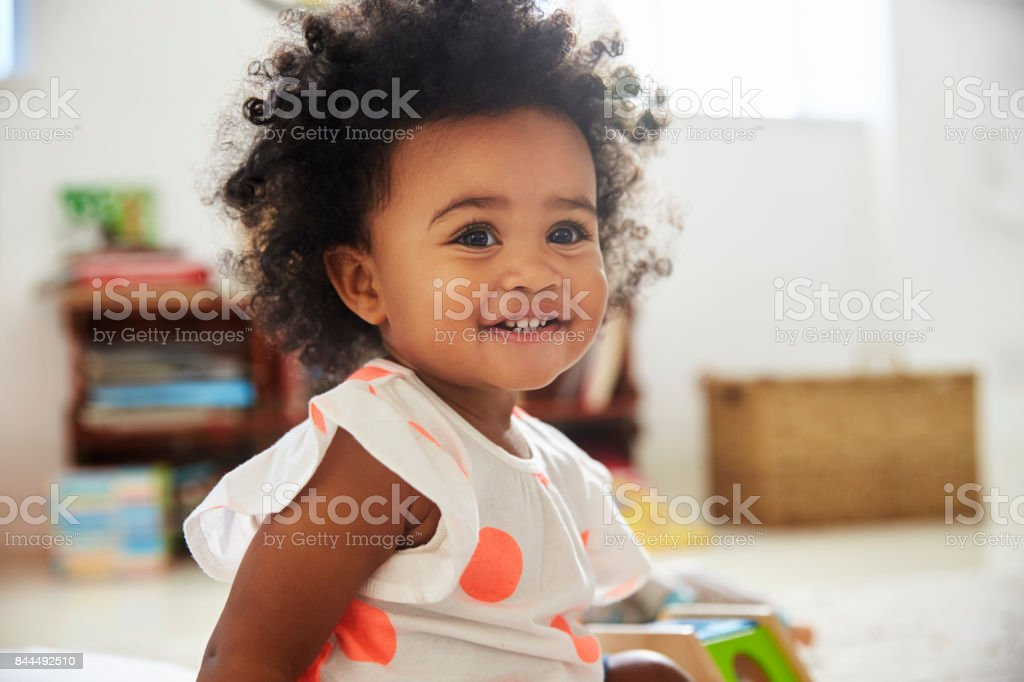 Happy Baby Girl Playing With Toys In Playroom stock photo