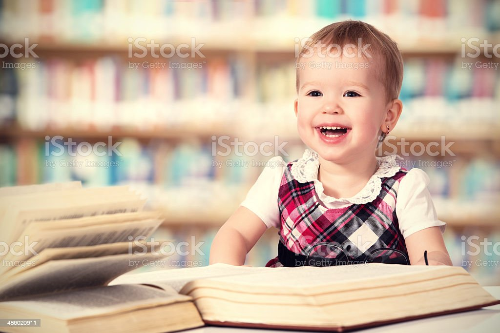 Happy baby girl reading a book in library royalty-free stock photo