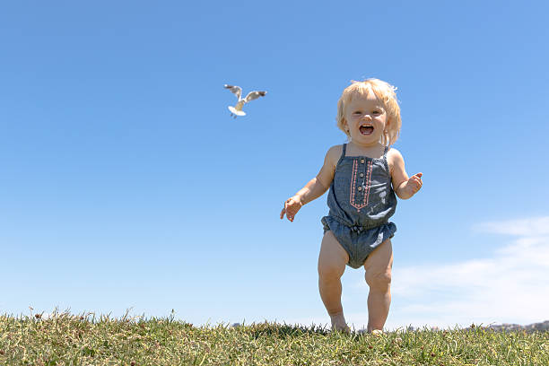 Happy baby girl runs on top of the hill stock photo