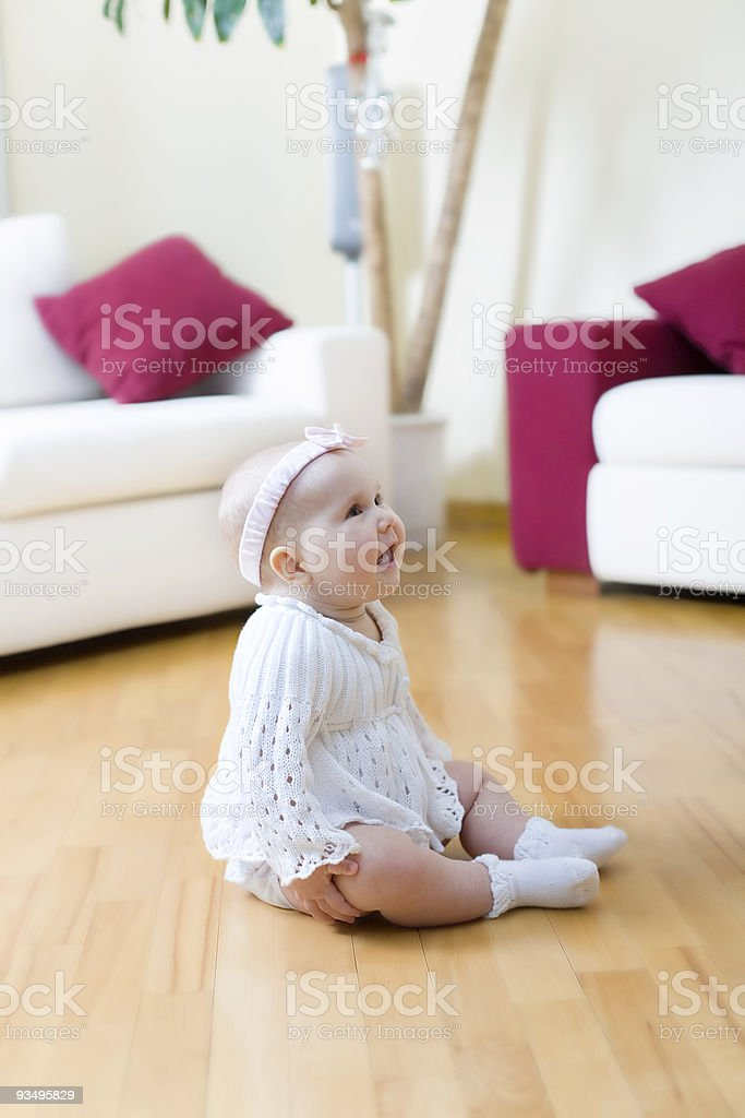 Happy baby girl seated on a floor in living room royalty-free stock photo