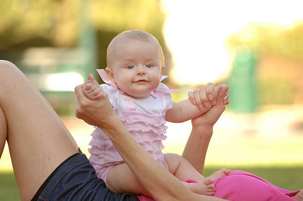 Happy Baby Girl Sitting on Mother's Belly. stock photo