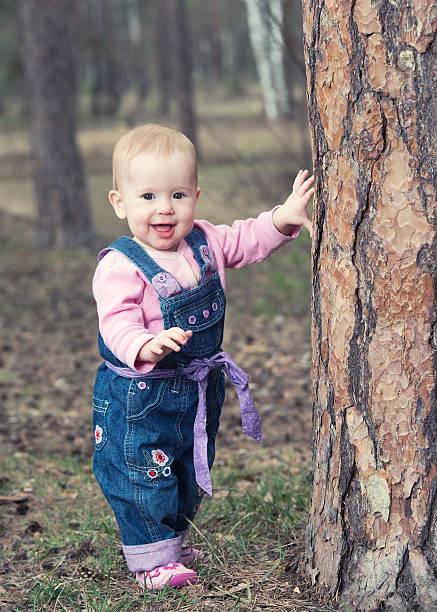happy baby mädchen steht in der nähe von einem baum an den beinen - jeans overall stock-fotos und bilder
