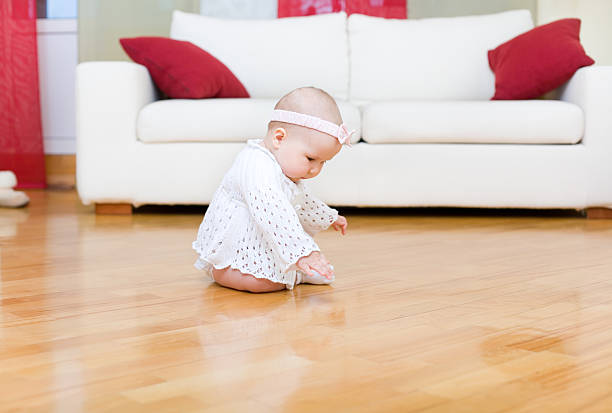 Happy baby girl touch a hardwood floor stock photo