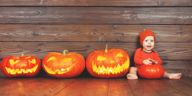Happy baby in costume for halloween with pumpkins on wooden picture id841337888?b=1&k=6&m=841337888&s=612x612&w=0&h=xyz6qt4ubci7evlndwabztjiz2f4erkbykhk12l7lns=