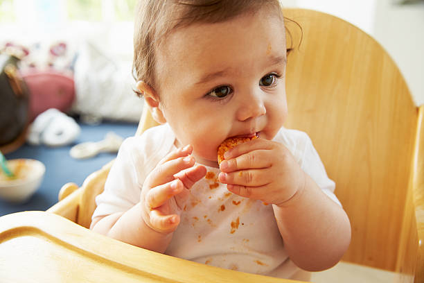 Happy Baby In High Chair At Meal Time stock photo