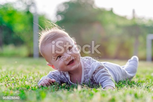 Cute funny laughing Caucasian baby boy learning to crawl, having fun playing on the lawn watching summer flowers in the garden during bright sunny day. Photo of smiling small 6 months old boy in green grass - he smiles and has fun while looking up. Happy young baby lying on tummy in nature.