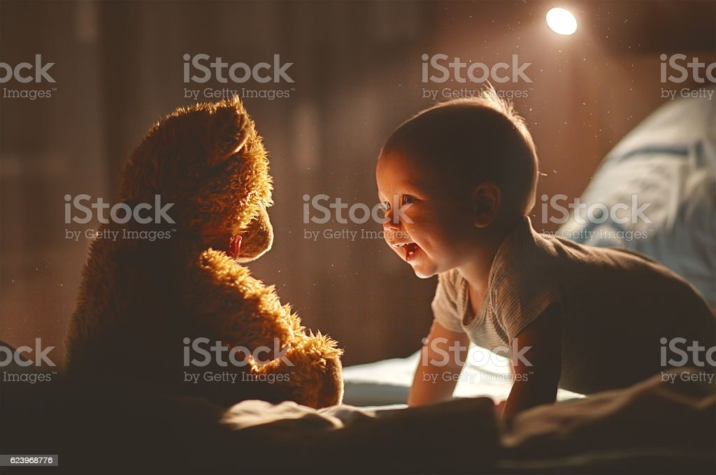 Happy baby laughing with teddy bear in bed stock photo