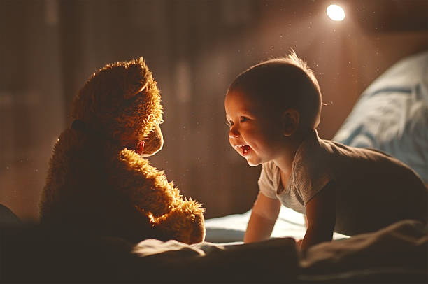 Happy baby laughing with teddy bear in bed - foto de stock