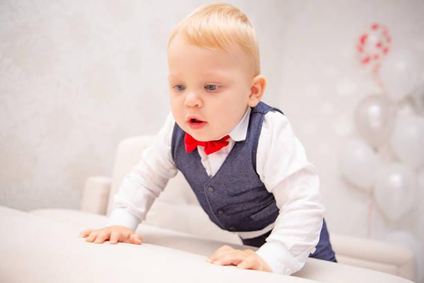 glückliches baby. kleiner junge in ein weißes hemd und fliege. kinder-porträt. stilvollen mann in modisch eine fliege. - sterntaufe stock-fotos und bilder