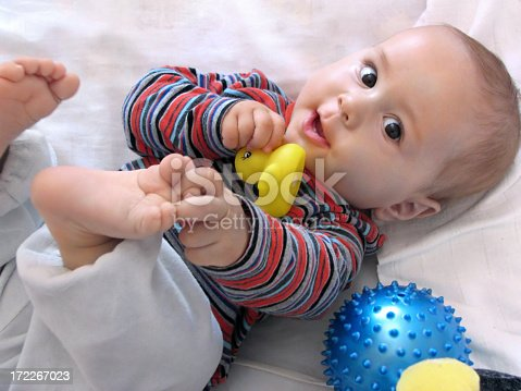 istock Happy baby looking at the camera while playing with his toes 172267023