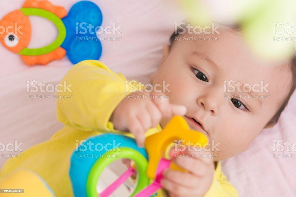 Happy Baby lag in seinem Bettchen Spielzeug aufmerksam betrachten – Foto