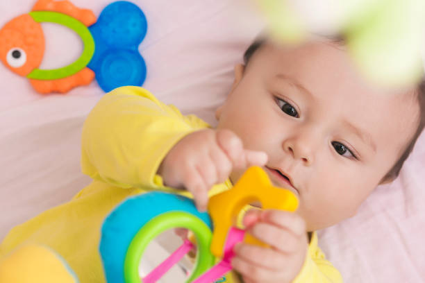Happy baby lying in his crib looking at toy intently stock photo