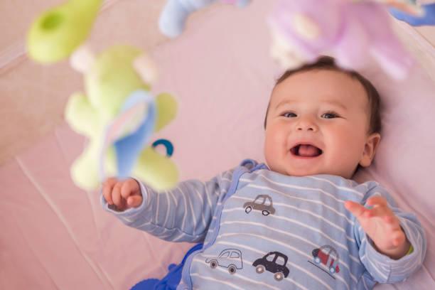 bebê feliz, deitado em seu berço sorrindo - mobile - fotografias e filmes do acervo