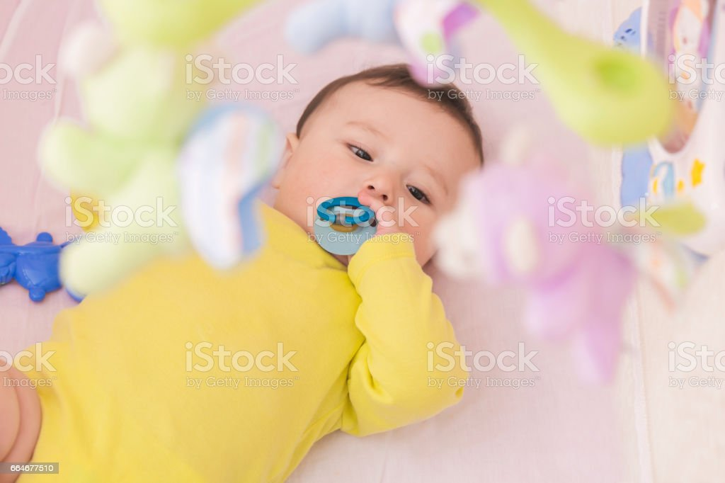 Happy baby lying in his crib sucking a pacifier stock photo
