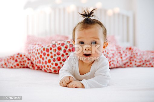 Adorable baby girl  is lying in the bed