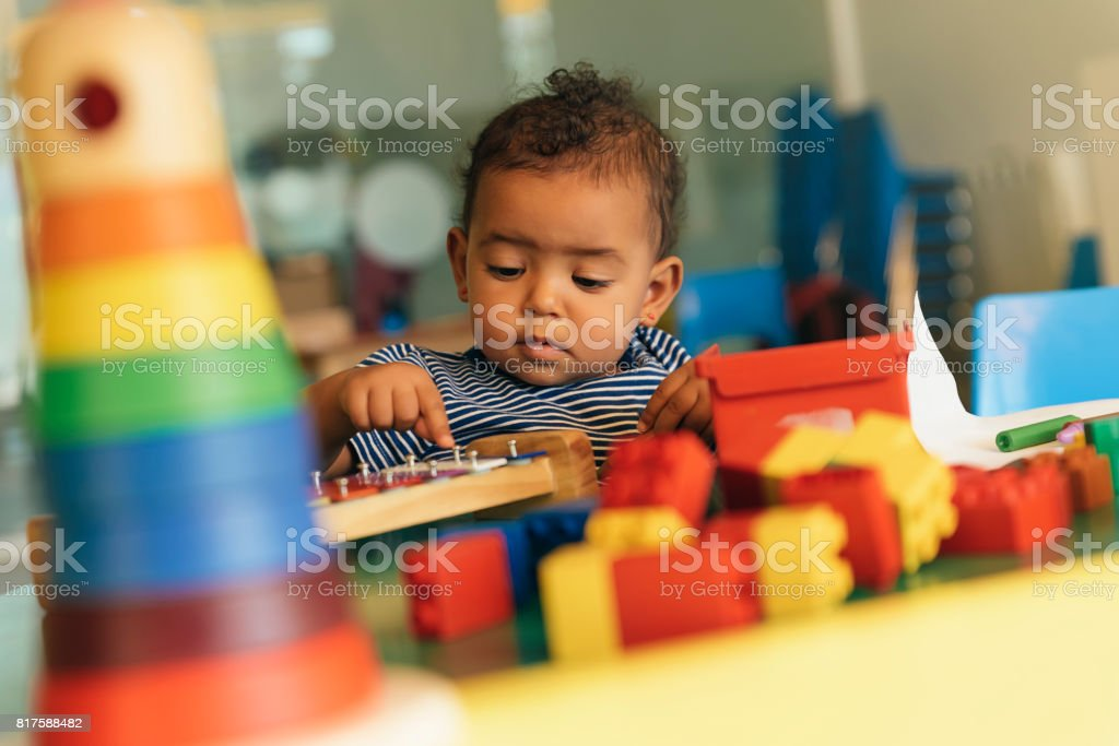 Happy baby playing with toy blocks. stock photo