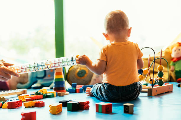 Happy baby playing with toy blocks. Happy baby playing with toy blocks in the kindergarten. preschool student stock pictures, royalty-free photos & images