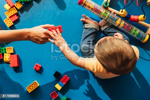 istock Happy baby playing with toy blocks. 817588604